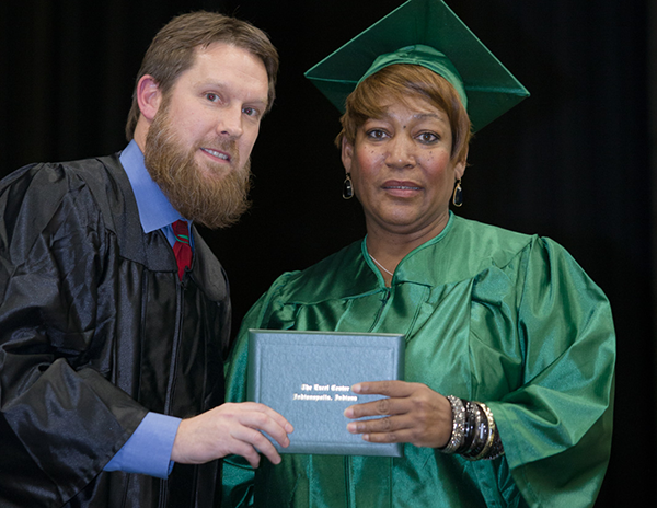 Brenda's coach at The Excel Center was proud to hand her her diploma