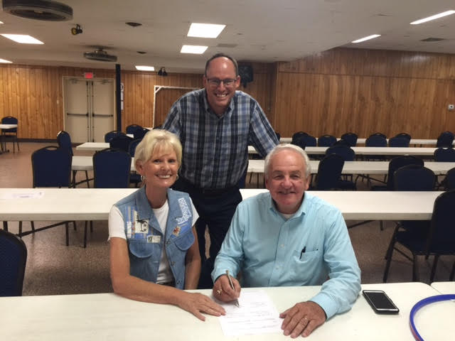 Goodwill CEO Kent Kramer and Candy Barksdale sign the merger agreement